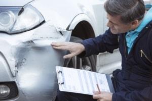Der Gutachter stellt am Auto die Unfallschäden fest und dokumentiert sie.
